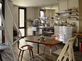 A Cherner Chair Retrospective - Photo 13 of 23 - Outfitted with shelves by EZ Shelving and a generic tool chest, the kitchen's galvanized steel integrated counter and sink was designed by Baker and fabricated by DeFauw Design + Fabrication. A vintage pair of Norman Cherner's Plycraft chairs and an A Chair by sustainable furniture-maker David Colwell surround a table by Pacassa Studios, which mounted a custom top on a Herman Miller Eames base. All appliances are electric, including heat-radiating panels, a combo washer-dryer unit, and an induction stove.