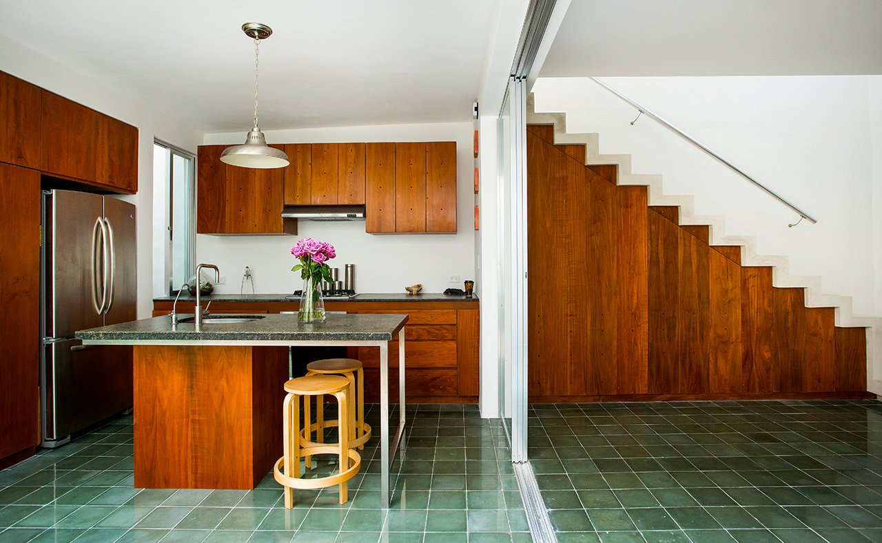 Handcrafted green cement tile floors are used in the kitchen and in many living spaces in the home. Honed granite counters, Tzalam wood cabinets, and GE Profile appliances complete the airy space.