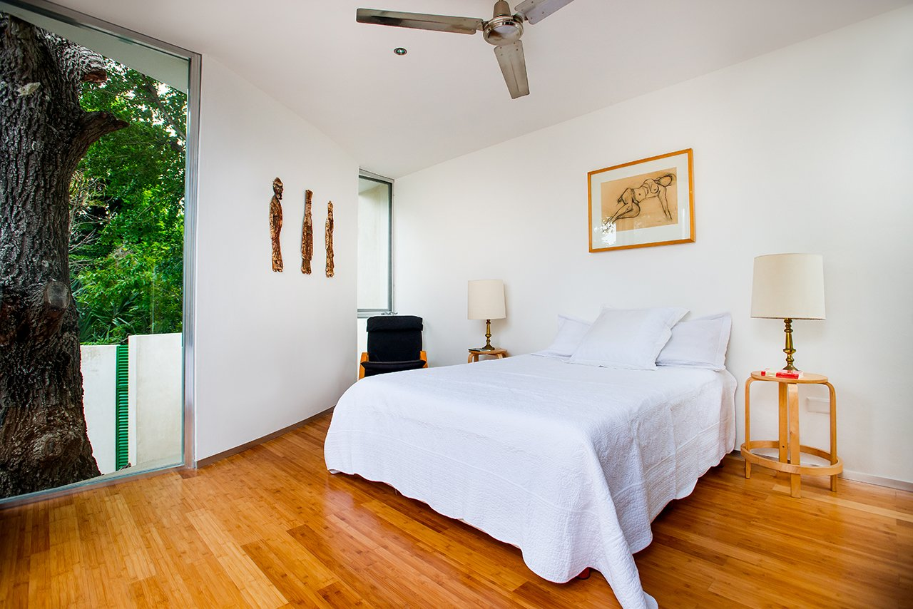 """Although the entire original structure of the house was preserved, an east-side addition adds space and is a distinctly modern counterpoint to the original home. The new construction, including the master bedroom, curves organically around the sapote tree, and the tree, says Salazar, """"becomes the main character.""""  Bedrooms by Dwell from Casa Mérida"""