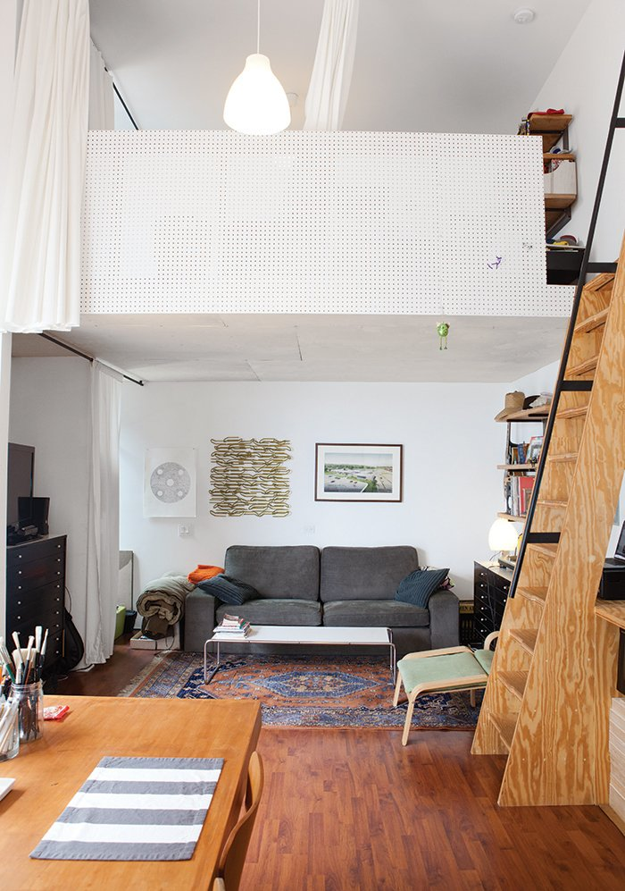 The living room is tucked beneath one of the lofts, which are accessible by a steep ladder-like staircase and fronted by pegboard.  Clever Loft Spaces for Small Places by Diana Budds from San Diego Teaches Us How Micro-Living Can Thrive