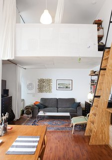 The living room is tucked beneath one of the lofts, which are accessible by a steep ladder-like staircase and fronted by pegboard.