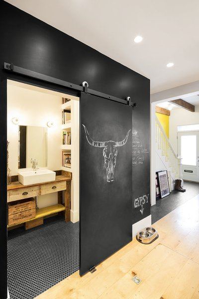 The chalkboard wall also acts as a sliding pocket door to the first floor bathroom. To maximize usable space, there are no hinged doors in the home's interior.