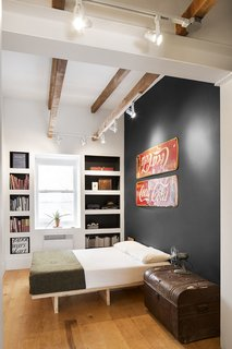An Old Row House in Montreal Gets a Colorful Modern Upgrade - Photo 9 of 10 - Boasting 11-foot ceilings, the master bedroom showcases and celebrates numerous antiques unearthed from the home during demolition. Midcentury enamel Coke signs, found under layers of rotting wood, became graphic accent pieces. A stately trunk, also uncovered from the renovation, is a centerpiece of the room and home, which is coincidentally located on Grand Trunk Street in the Pointe-Saint-Charles neighborhood of Montreal.