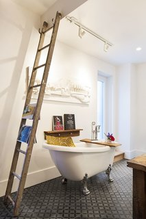 An Old Row House in Montreal Gets a Colorful Modern Upgrade - Photo 10 of 10 - A new clawfoot tub sits next to an old wooden ladder that serves as a towel and magazine rack.
