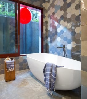 One Home, Three Bathrooms, Each with an Awesome Way to Use Tile - Photo 2 of 3 - The master bathroom's Aquabrass tub is next to a window lined by fumed oak millwork framing a tethered red balloon, displayed for levity.