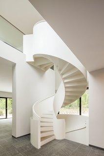 10 Dazzling Modern Staircases - Photo 1 of 10 - A sculptural white steel spiral staircase with wooden treads connects a lower level to an upper cantilevered level in this home near Potsdam, Germany, that was designed by Nps Tchoban Voss. The slim profile of the steel contrasts with the undulating curves of the powder-coated steel railing.