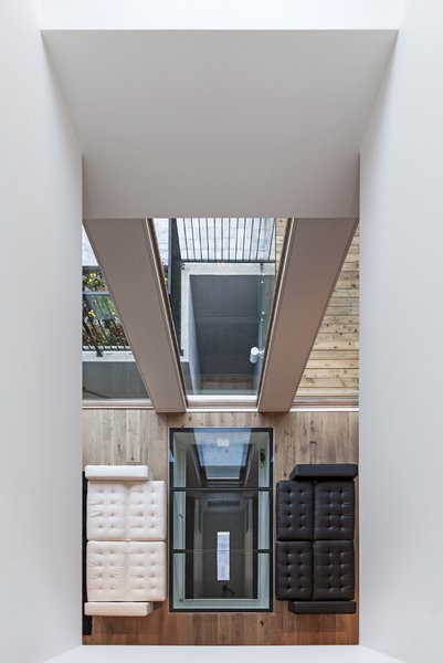 Looking downwards from the second floor, the void creates an invisible barrier between the family room and the living area. The reflection from the skylight exaggerates the idea of an even more depth within the house.