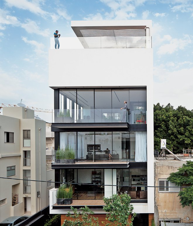 Tall and surprisingly open, the Tel Aviv Town House by Pitsou Kedem Architects continues in the tradition of its Bauhaus-inspired neighbors with a white facade and black window frames.  Minimalist Facades We Love by Zachary Edelson from Modern Courtyards Part Two