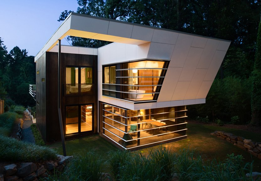 The house features a concrete rainscreen painted gray and Cor-Ten steel paneling around the exterior of the bedrooms. The horizontal louver theme around the dining room windows mimics the vocabulary established on the street-facing facade.  Photo 2 of 7 in An Angular Futuristic House in Georgia