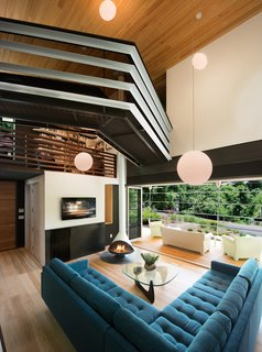 """In the living room, Svenson opted for wide-plank ash floors and a fireplace from Malm. The room connects to the screened-in porch (accessed by folding doors) and has a view of the split-levels above. The jagged bridge leads to the residents' writing studios. """"I wanted something that feels a little scary, that gives you energy when you walk across it,"""" says Svenson."""