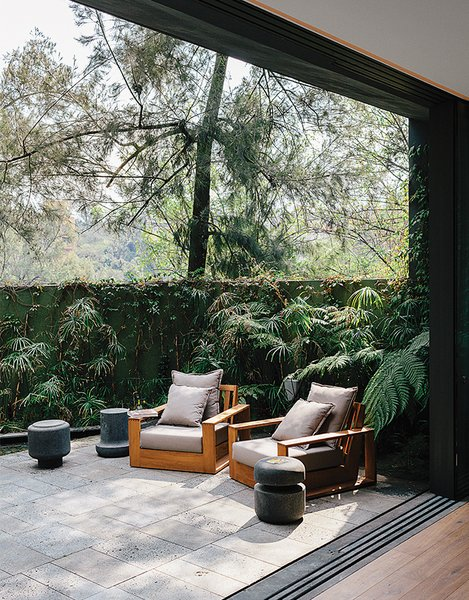 Recinto lava stone lines a patio adjacent to the living room in designer Ezequiel Farca's house in Mexico City. He designed the teak outdoor furniture, including two arm-chairs.