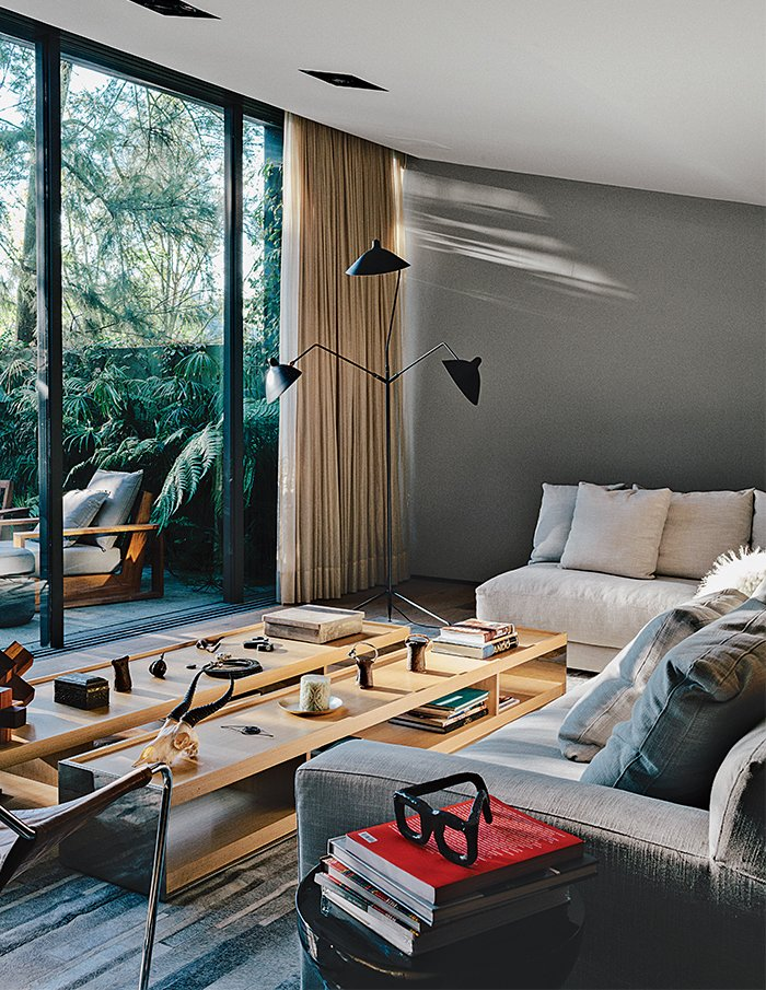 Farca furnished the living room with a Serge Mouille three-arm floor lamp, custom sofas from EF Collection, and Surface tables by Vincent Van Duysen for B&B Italia. Tagged: Living Room, Sofa, Coffee Tables, and Floor Lighting.  Photo 4 of 15 in A Lush Retreat With a Sheltered Rooftop Pool in Mexico City