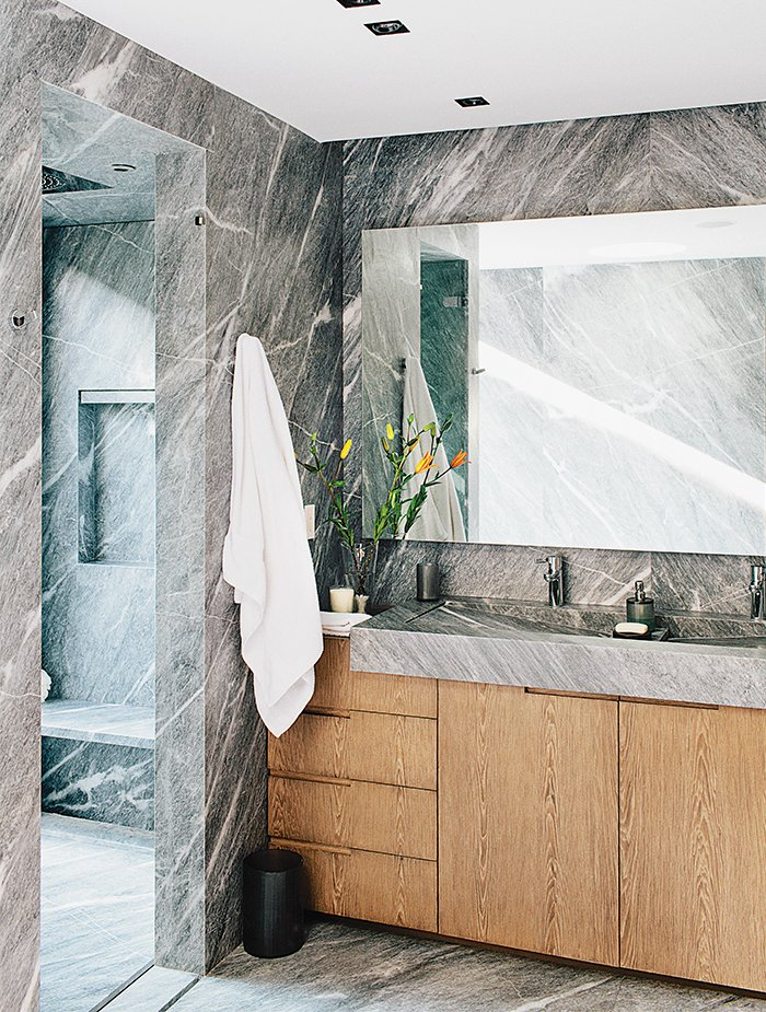 The striking master bath is lined from floor to walls in silvery gray marble. Tagged: Bath Room, Marble Counter, Ceiling Lighting, and Marble Wall.  Photo 8 of 15 in A Lush Retreat With a Sheltered Rooftop Pool in Mexico City