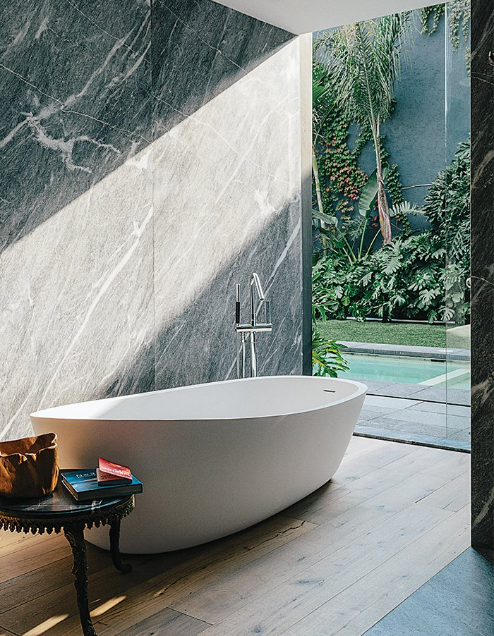 An Almond bathtub by Porcelanosa is accented by a tub filler from Hansgrohe. Tagged: Bath Room, Medium Hardwood Floor, Freestanding Tub, and Marble Wall.  Photo 9 of 15 in A Lush Retreat With a Sheltered Rooftop Pool in Mexico City