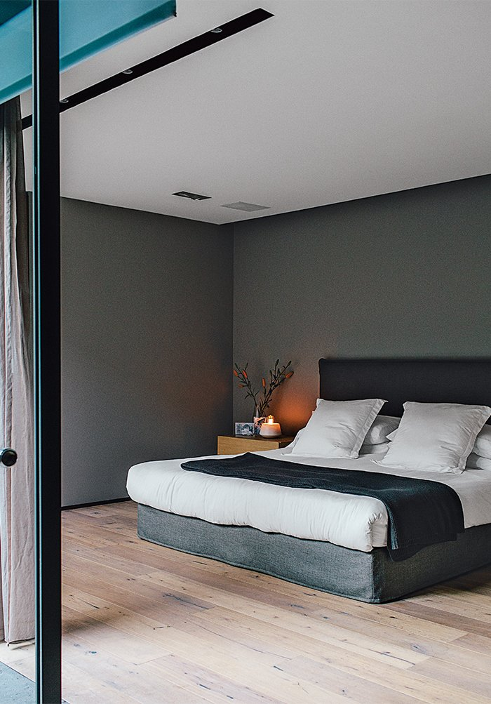 The master bedroom, painted in Whisper by Comex, sports a bed that Farca custom-designed as part of his EF Collection. Tagged: Bedroom, Bed, and Light Hardwood Floor.  Photo 10 of 15 in A Lush Retreat With a Sheltered Rooftop Pool in Mexico City