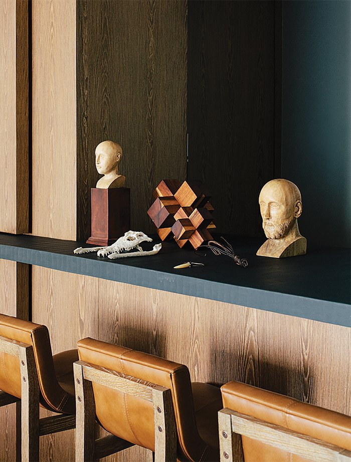 In the dining room, antique wooden busts and a machiche cross designed by Farca are arranged on a resin countertop by Monica Calderon. The bar conceals a service area with an espresso machine. Tagged: Dining Room and Stools.  Photo 14 of 15 in A Lush Retreat With a Sheltered Rooftop Pool in Mexico City