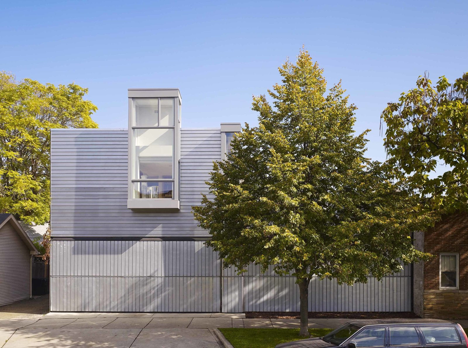 """The new two-story addition is clad in the same metal decking as the original one-story home. Principal Joe Valerio says this kind of decking is usually crafted using ribs of equal width to create a highly articulated surface. To avoid that look, he used ribs that alternate between very narrow and broad widths, to create a façade that """"has a monolithic quality.""""  Photo 1 of 6 in A Two-Story Addition Turned a Bachelor Pad Into a Comfortable Home For Two"""