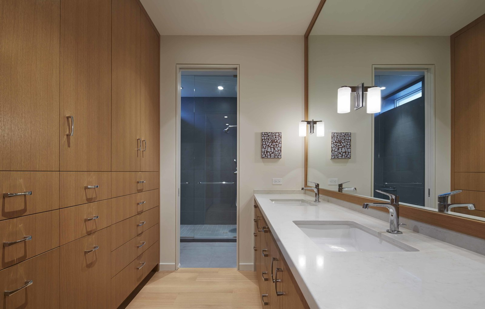 "The master bathroom strikes a balance between the desires of both parties. Warm wood cabinets and floors mingle with the darker glass and stone setup in the shower area. ""Although this was very much Lisa's addition, there was an understanding between the two that Bruce had to be part of it,"" Valerio says.  Photo 6 of 6 in A Two-Story Addition Turned a Bachelor Pad Into a Comfortable Home For Two"