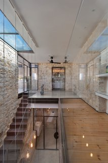 """A 250-Year-Old Stone House in Israel With a Surprisingly Modern Interior - Photo 1 of 7 - The original home was built in the shape of the Hebrew letter """"Chet,"""" which wrapped around an open courtyard. The courtyard was closed off to become flexible public space, and now lies in between two private living areas. A steel and wood bridge connects the private wings of the home, which consist of bedrooms, bathrooms, and working spaces for the residents."""