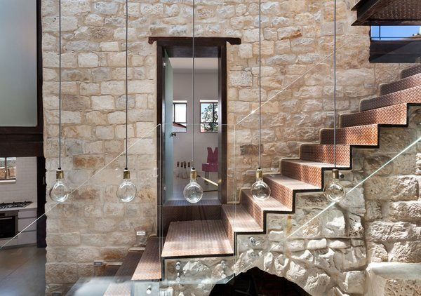 The walls are made of recycled limestone sourced locally from dismantled houses. The stone staircase, original to the home, was kept intact and wrapped in tin boards. Though it used to lead to the home's roof, it now connects the kitchen and dining area with a new addition above. The door frame of the guest unit is fabricated in varnished steel to complement the natural beauty of the surrounding stone.