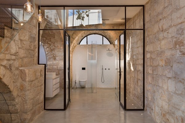 The master bathroom is framed by a glass and varnished steel doorway. Minimal white tiling and concrete floors allow both the original stone walls and graphic geometric glass openings to take center stage.