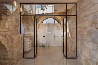 A 250-Year-Old Stone House in Israel With a Surprisingly Modern Interior - Photo 6 of 7 - The master bathroom is framed by a glass and varnished steel doorway. Minimal white tiling and concrete floors allow both the original stone walls and graphic geometric glass openings to take center stage.