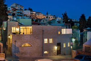A 250-Year-Old Stone House in Israel With a Surprisingly Modern Interior - Photo 7 of 7 - The historic facade blends in with the new stone of the addition. Several balconies on the upper level encourage outdoor living, and enable movement between the two private wings of the home. Situated on a hill in the old historic district, sweeping views are enjoyed from these private outdoor retreats.