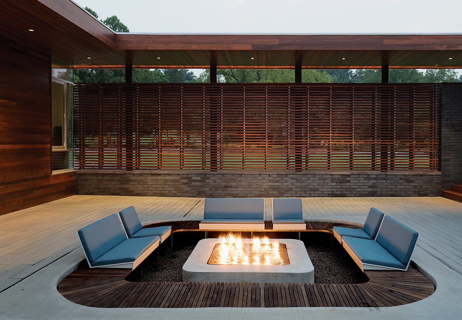 Taking cues from a Japanese-influenced slatted screen applied to the house's facade, Hufft Projects applied a ring of ipe wood around the perimeter of this outdoor firepit. Tagged: Outdoor, Back Yard, Concrete Patio, Porch, Deck, Wood Patio, Porch, Deck, Horizontal Fences, Wall, and Wood Fences, Wall.  Photo 11 of 11 in Take it Outside With These 11 Spring-Friendly Deck Spaces from Slat Happy: 8 Louvered Homes
