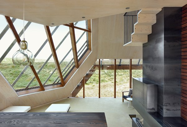Each room in the interior was carefully curated to reflect the unique function of that space. The interior interacts intimately with the surrounding landscape, as different visual perspectives of the dunes are framed by the geometric facade. Photo 4 of Dune House modern home