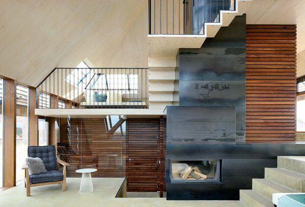 "The interior staircase spirals around the center of the home, in a ""promenade architecturale"" connecting each level. The continuous and gradual vertical movement is a subtle nod to the experience of strolling through the dunes. A central wood-burning fireplace efficiently heats the whole home, minimizing the need for supplemental in-floor heating incorporated in the concrete floors. Natural cross-ventilation is achieved through the use of CO2 directed grills at the north and south of the home, an added green feature that further reduces the ecological footprint. Photo 5 of Dune House modern home"