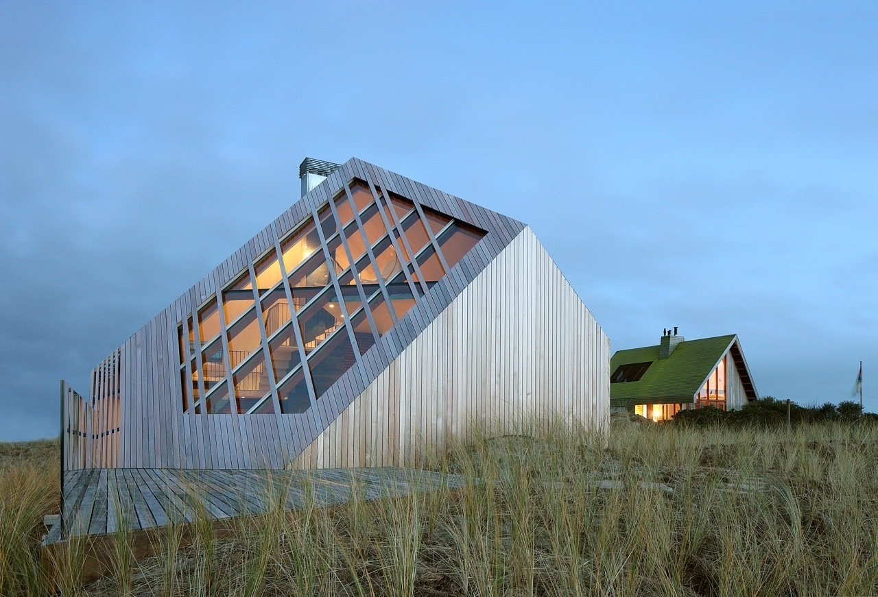 Illuminated at dusk, the home brings light and energy to the sleepy dunes. Relying on cues from the natural beauty of the surrounding landscape, the home quietly but confidently makes its presence felt.  Dune House by Sarah Akkoush