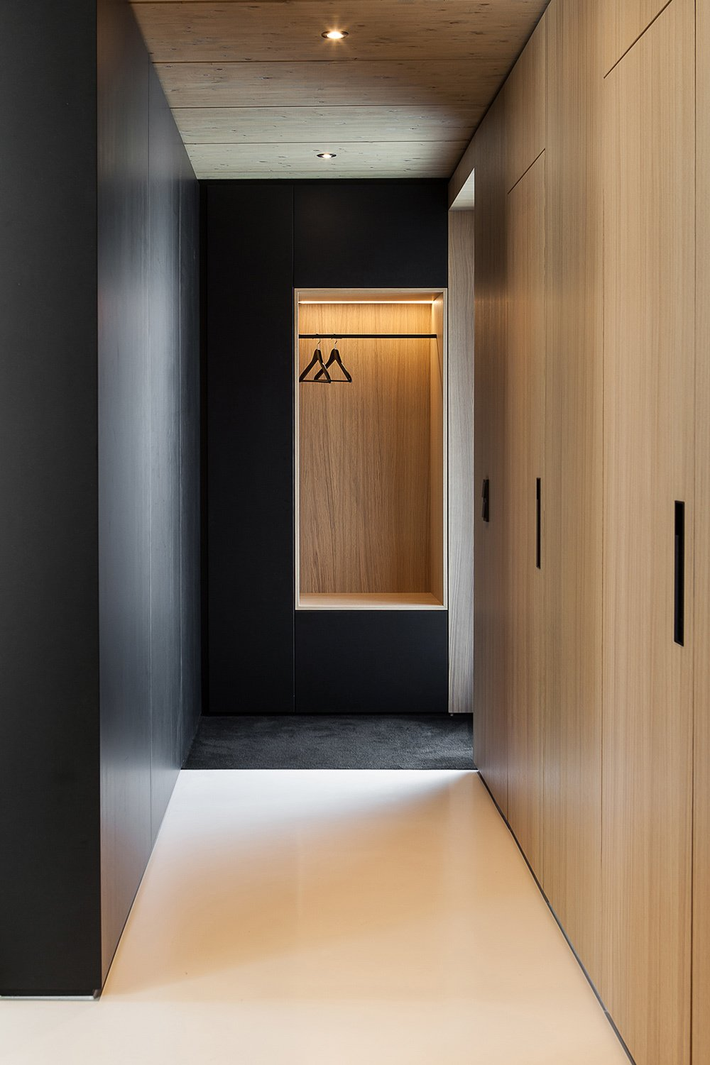 Custom built-in furniture takes design cues from the home's timber frame. The staircase and all built-in storage objects are made of wood. Two black wood units separate the stairwell from the living room and kitchen.