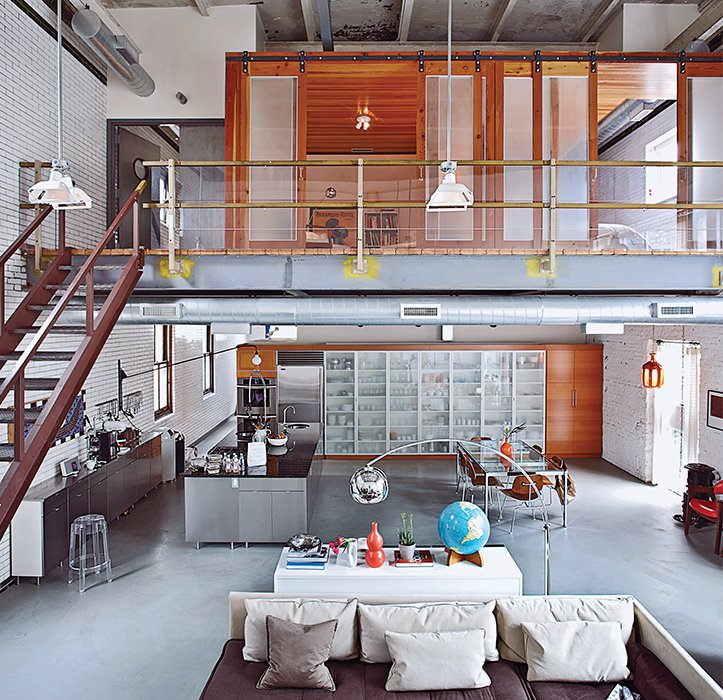 Downstairs, century-old subway tile and copper windows keep the new kitchen gritty; it gained a stainless-steel island, new appliances, and a wall of IKEA storage.  Remarkable Brick Homes by Luke Hopping from Raw Materials Connect this Chicago Renovation with its Industrial Past