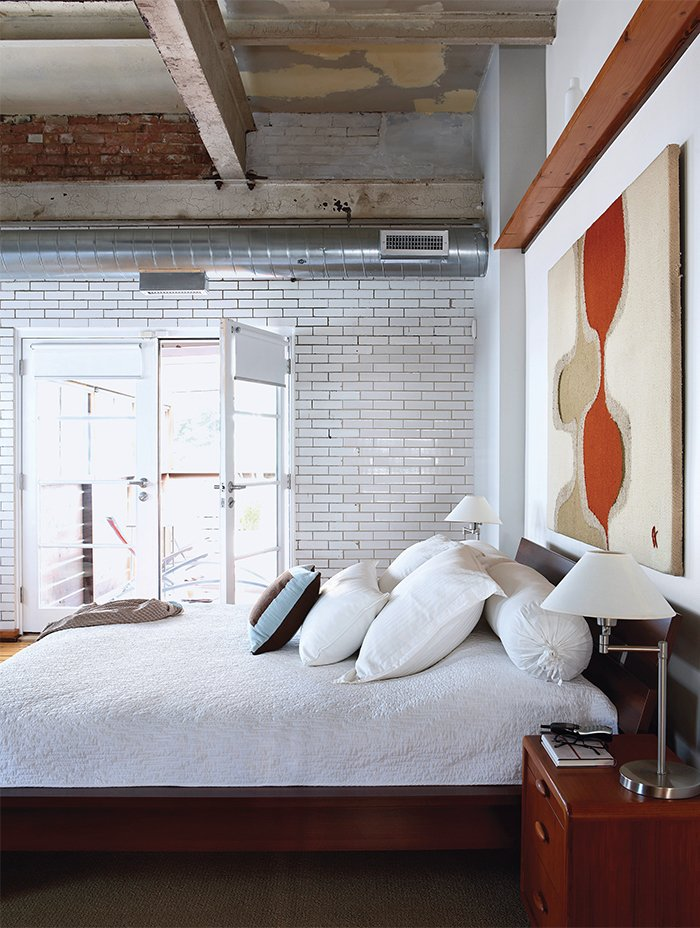Like the communal spaces, the bedroom features a shining subway tile wall. Tagged: Bedroom and Bed.  Bedrooms by Dwell from Raw Materials Connect this Chicago Renovation with its Industrial Past