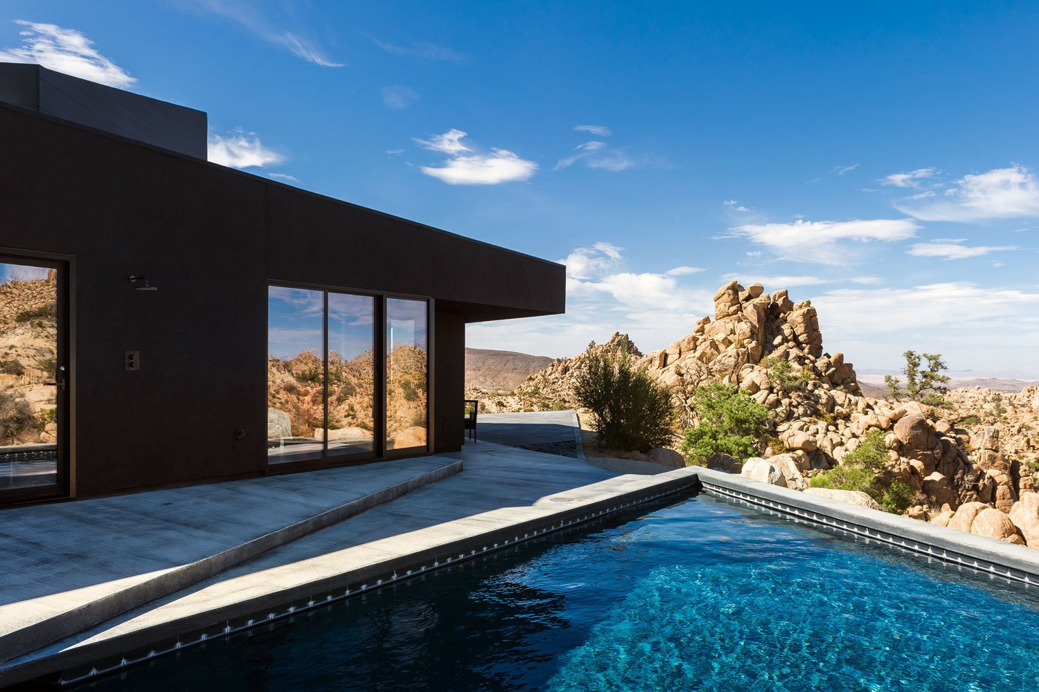An unadorned black façade echoes the homeowners' brief but compelling instructions to the architects to design a house like a shadow.  Photo 4 of 8 in A Sculptural Desert Escape Inspired by a Shadow