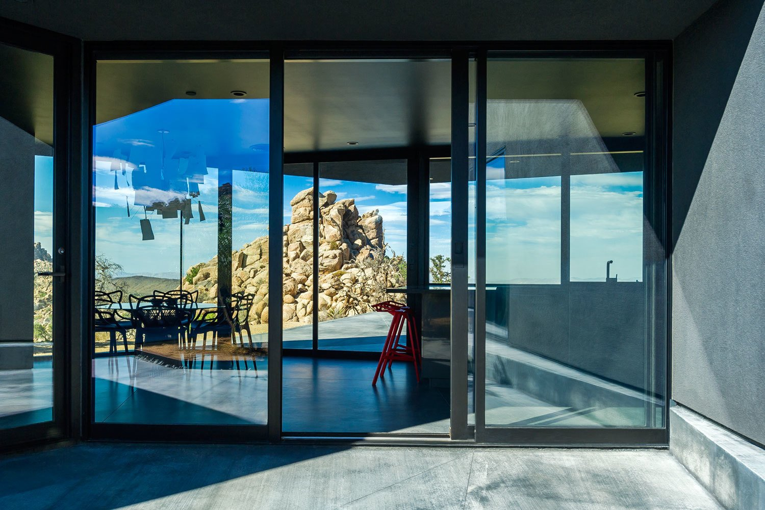An enormous boulder blocks views of the street, enhancing the sense of tranquility. Tagged: Windows, Metal, and Sliding Window Type.  Photo 7 of 8 in A Sculptural Desert Escape Inspired by a Shadow