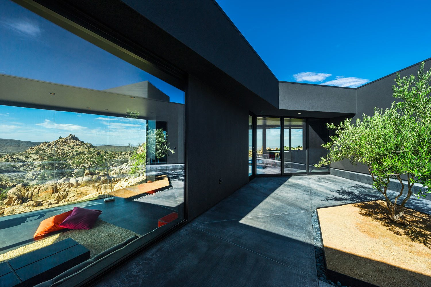 The architects designed the rooms as a linear sequence wrapping around a central courtyard. As one would have traversed the preexisting rock face, residents are constantly negotiating small elevation changes throughout the house. The plan also protects a central courtyard from the harsh Yucca Valley climate.
