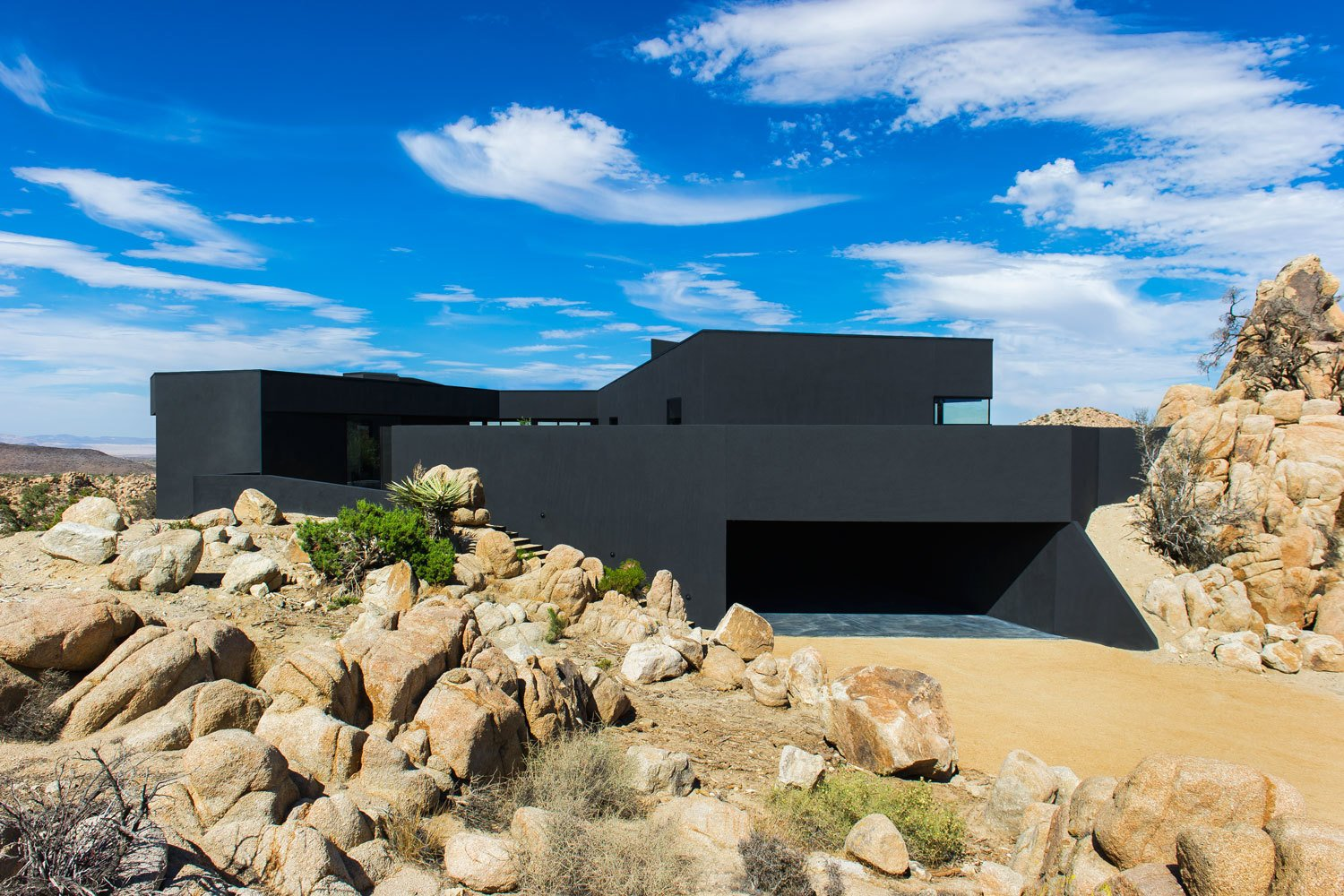 The house seems to claw onto the surrounding landscape, nestled on an outcropping with nearly 360 degree views of the surrounding desert.