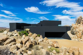 A Sculptural Desert Escape Inspired by a Shadow - Photo 8 of 8 - The house seems to claw onto the surrounding landscape, nestled on an outcropping with nearly 360 degree views of the surrounding desert.