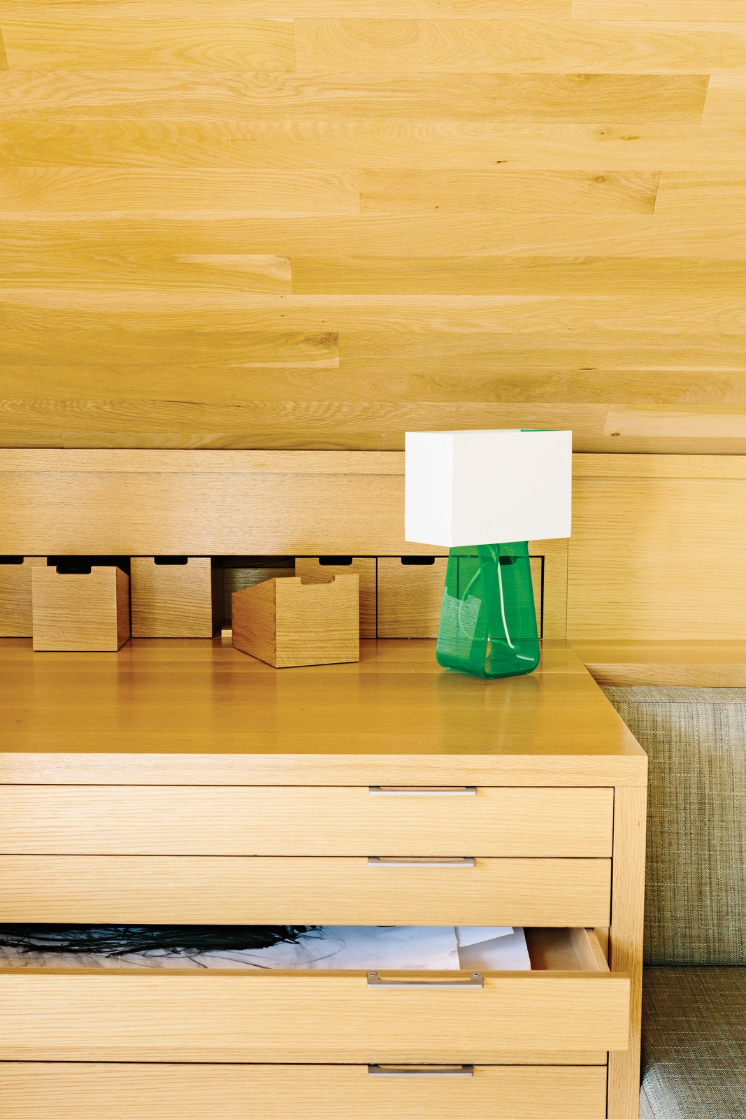 The main built-ins—a sofa bed, table and chairs, and plenty of storage—run the length of the space and are tucked snugly beneath the ceiling. The green Tube Top 14 lamp by Pablo Pardo is from Relish Design. Tagged: Storage Room and Cabinet Storage Type.  Best Photos from Salvaged Wood Renovation in Portland