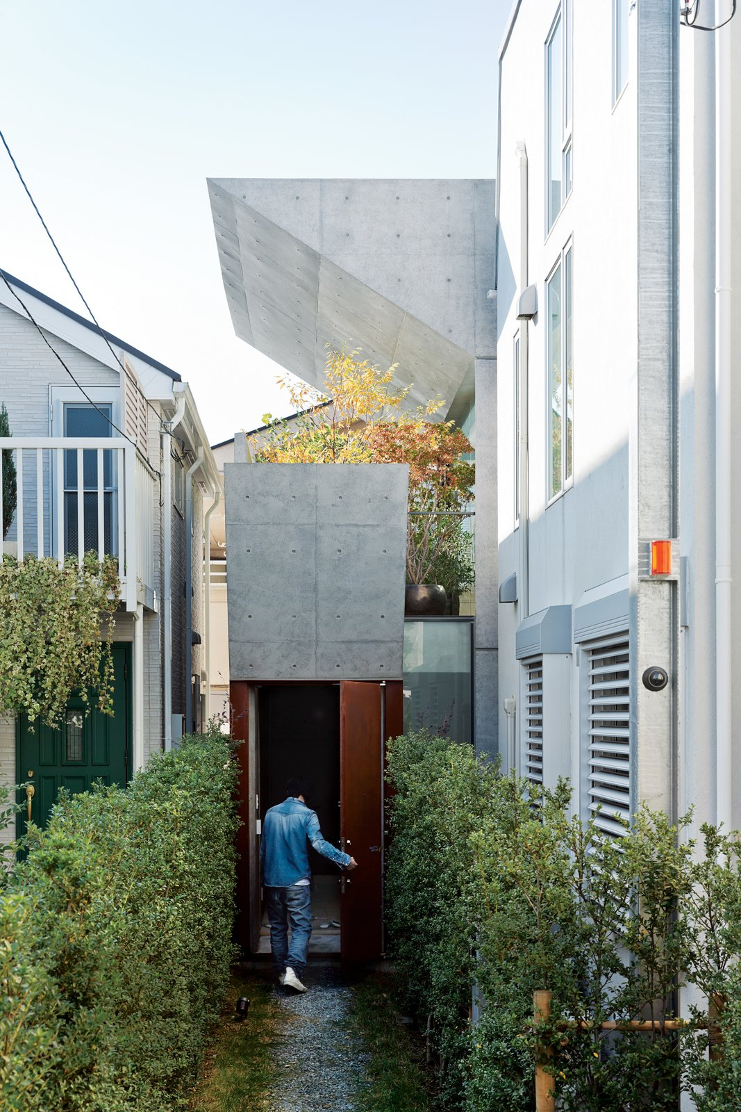 After purchasing a thin, L-shaped lot in Tokyo, Tamotsu Nakada asked architect and friend Koji Tsutsui to create an open-plan concrete home to fit the site. Tagged: Outdoor, Walkways, Side Yard, Gardens, Shrubs, Front Yard, and Garden.  Photo 1 of 7 in Open-Plan Concrete Home in Japan