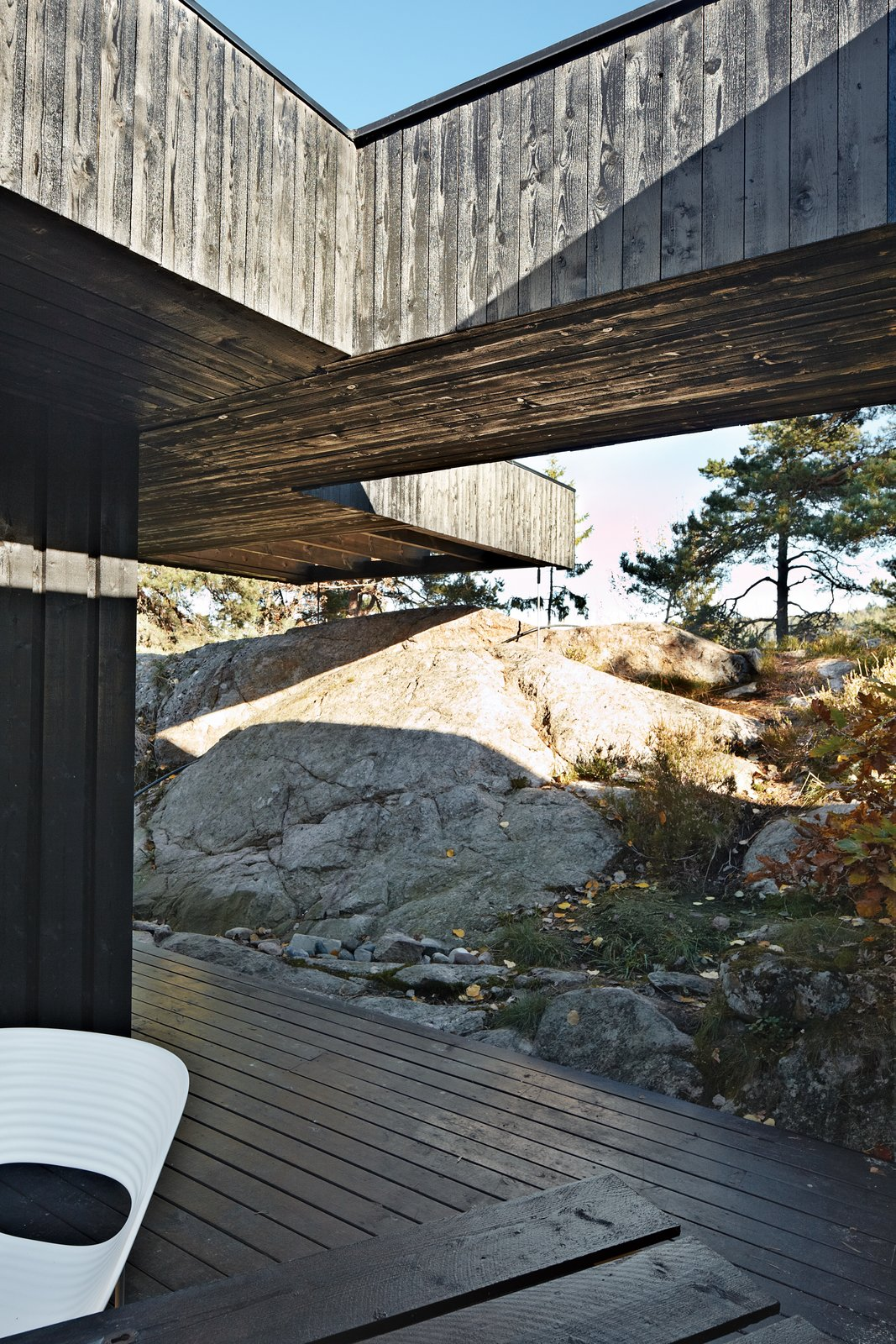 A section of the roof reaches over a rock outcropping—a detail that visually connects the house to the landscape and offers a handy way to climb up to the roof deck without using a ladder. Tagged: Outdoor, Boulders, Large Patio, Porch, Deck, Wood Patio, Porch, Deck, and Trees.  Cabins & Hideouts by Stephen Blake from 430 Cabin