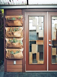 The area includes a Wally planter from Woolly Pocket near the custom steel-and-glass doors.