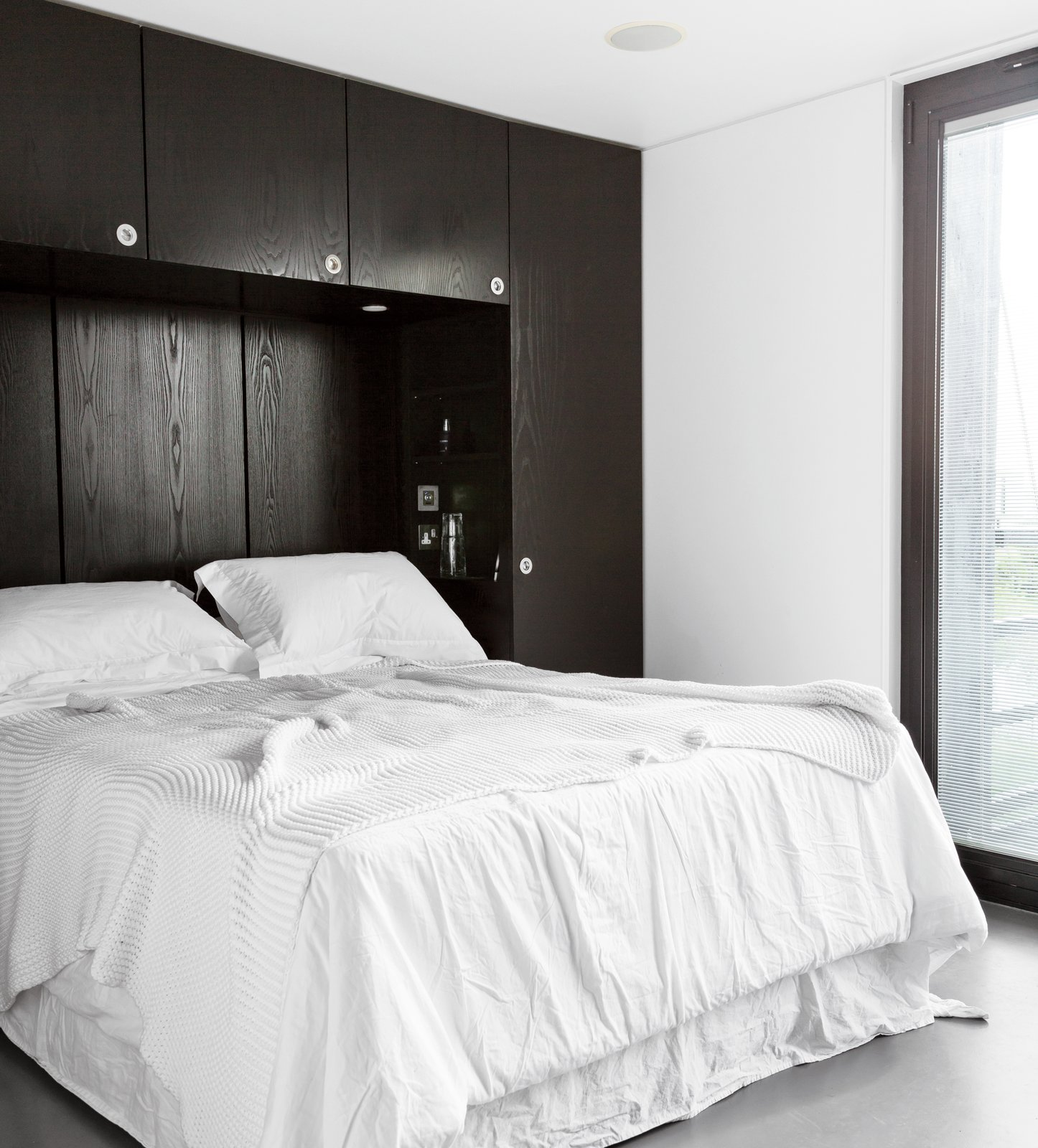The master bedroom echoes the house's black-and-white exterior and includes a custom-built storage unit that the architect designed for the space. Tagged: Bedroom, Bed, Concrete Floor, and Storage.  Photo 5 of 7 in An Elevated Deckhouse in England