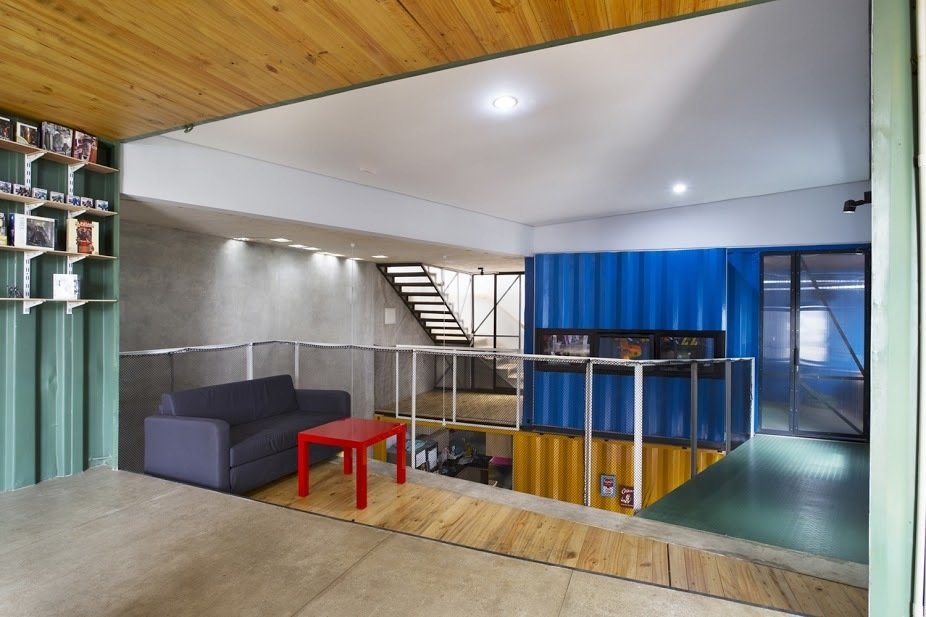 Natural light pours into the open-plan house, which is outfitted with low-cost materials like polished concrete floors and recycled metal railings.  Shipping Containers by Dwell from In Indonesia, a Green-Roofed Container Home Stands Up to the Heat