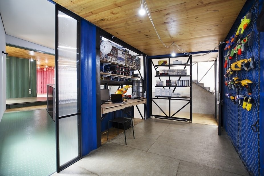 The hobby room features a custom desk and shelving system that Atelier Riri designed and manufactured themselves. A custom frame holds the family's tools and other objects on the eastern wall.  20 Ideas On What You Can Do With Old Shipping Containers by Luke Hopping from In Indonesia, a Green-Roofed Container Home Stands Up to the Heat