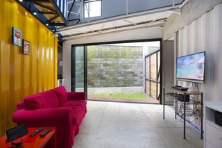 How to Stay Cool by Living in a Shipping Container - Photo 7 of 10 - A sliding glass door in the downstairs living room leads to an outdoor patio and green space. A sofa and side table from IKEA complement an unfinished wood entertainment center.