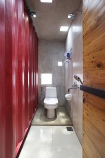 How to Stay Cool by Living in a Shipping Container - Photo 8 of 10 - In one of the home's three bathrooms, a TOTO toilet is illuminated by LED light fixtures from OSRAM. Simple square-shaped skylights and windows allow natural light to fill the space.