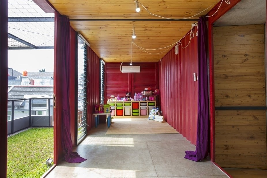 A cherry red game room gives way to a second green space on the roof, which can be used as an extension of the indoor space. Tagged: Kids Room, Playroom, Storage, Concrete Floor, Toddler Age, Neutral Gender, and Pre-Teen Age.  Amazing Examples of Shipping Container Architecture by Diana Budds from In Indonesia, a Green-Roofed Container Home Stands Up to the Heat