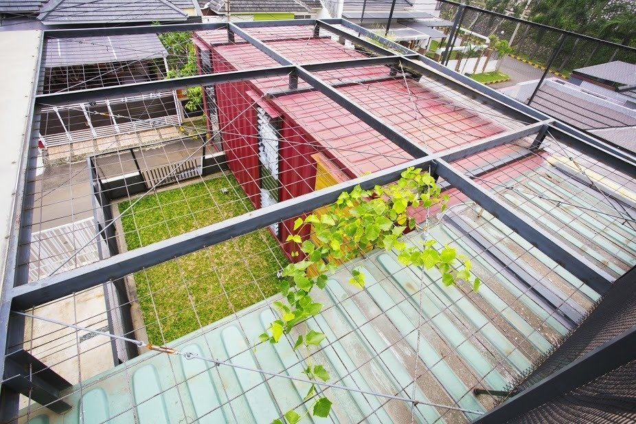 Covered with wire mesh, the green roof will continue to vegetate over time.  Shipping Containers by Dwell from In Indonesia, a Green-Roofed Container Home Stands Up to the Heat